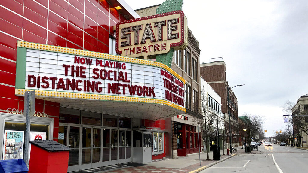 A movie theater marquee displays the message The Social Distancing Network.